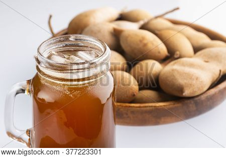 Tamarindus Indica - Tamarind Juice In A Glass Surrounded By Fresh Ripe Tamarinds