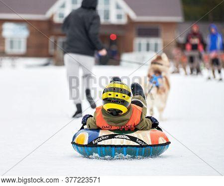 Verkhoshizhemye, Russia - 03.07.2020 - Little Kid On Snow Tubing With Sled Dog. Koltco Fortuny - Fun