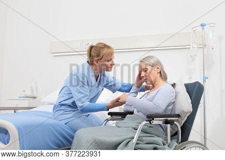 Nurse Take Comfort Sad And Pensive Elderly Woman Isolated On Wheelchair Near Bed In Hospital Room, C