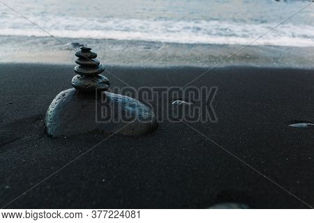 Stones Heap Built Tower On Beach Wet Sand And Sea Water Tenerife Island, Spain Side View Closeup Cop