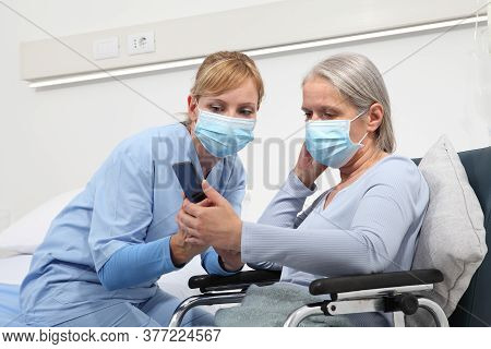 Nurse Helps With Cell Phone To Contact The Elderly Lady's Family In The Wheelchair, Wearing Surgical