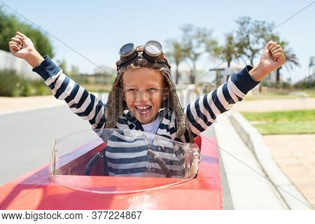 Happy laughing boy raising hand in victory after riding gokart outdoor. KId having fun and driving toy race car on street. Child exult while riding an electric or peddle toy auto wearing pilot helmet.