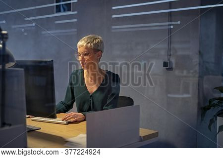 Overworked young businesswoman working on computer at office. Beautiful tired business woman working on assignment at night. Creative girl using computer late at night, overload and business deadline.