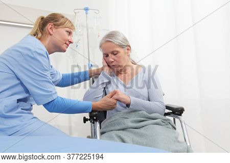 Smiling Nurse Take Comfort Elderly Woman Isolated On Wheelchair Near Bed In Hospital Room, Concept O