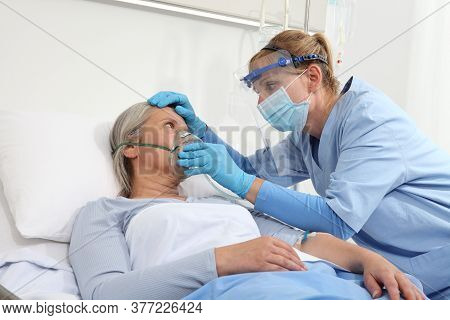 Nurse Puts Oxygen Mask On Elderly Woman Patient Lying In The Hospital Room Bed, Wearing Protective G