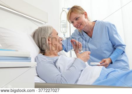 Nurse Gives The Pill To The Elderly Woman Patient Lying In The Hospital Room Bed, Concept Of Lonelin