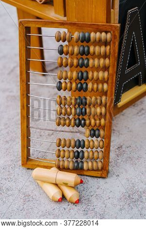 Big Wooden Abacus At Chalkboard Crayon Set Outside. School Supplies Calculator Frame Sample On Groun