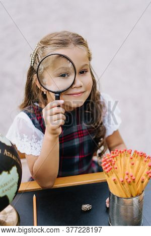 Pretty Primary Schoolgirl Look Through Magnifier. Little Caucasian Girl Smile Hold Loupe Sit At Desk