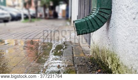 Rain Water Is Pouring From The Green Draining Gutter On The Pavement, Selective Focus