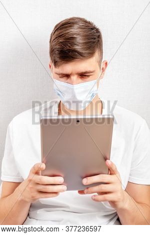 Young Man In Flu Mask With A Tablet By The Wall In The Room
