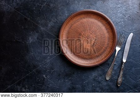 A Beautiful Plate For Food, A Dish, Browns, A Fork, A Knife, Against A Dark Background.