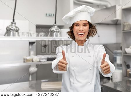 cooking, gesture and people concept - happy smiling female chef in toque showing thumbs up over restaurant kitchen background