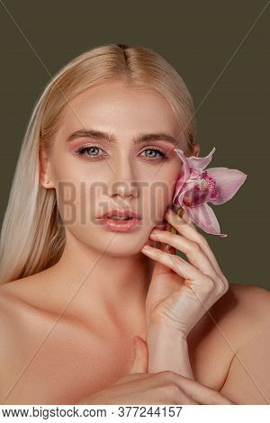 Beauty Portrait. Ayurveda Treatment. Blonde Woman Touching Face Skin With Orchid Flower Isolated On