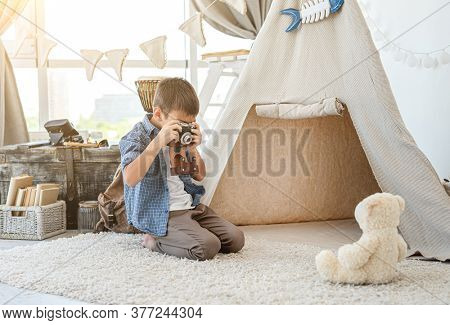 Little boy taking picture of plush teddy with retro camera in playroom