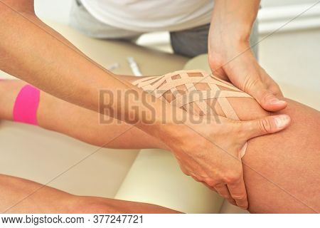 Young Female Physiotherapist Applying Kinesiology Tape And Massaging Knee Of Her Patient, Closeup De