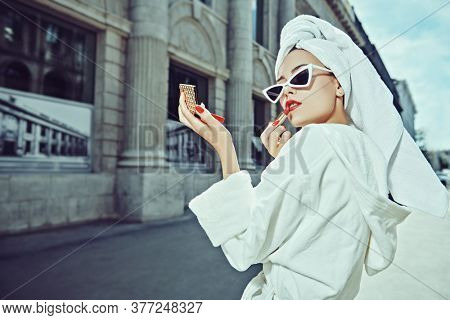 Glamorous lifestyle. Stunning woman in a white bathrobe with a white towel on her head is doing make up on a city street. Fashion shot.