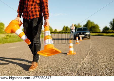 Male instructor puts cones on road, driving school
