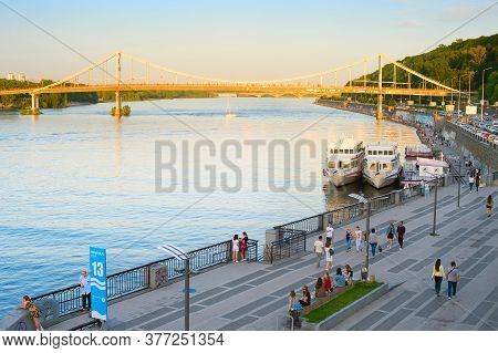 Kiev, Ukraine - June 08, 2020: People Walking By The River Dnipro Embankment At Sunet. Pedestrian Br