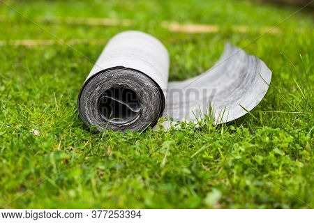 Roll Of Roofing Felt Close-up. Ruberoid On The Green Grass. A Beautiful Image Of Building Material.