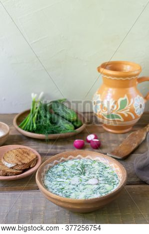 Okroshka, A Traditional Dish Of Russian Cuisine. Cold Soup In A Deep Plate With A Jug On A Wooden Ta