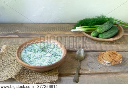Okroshka, A Traditional Dish Of Russian Cuisine. Cold Soup In Pottery On A Wooden Table With Ingredi