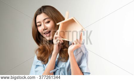 Portrait Of Young Beautiful Asian Woman Holding The Wooden House Model Feeling Happy And Joyful To S