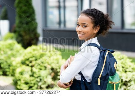Side View Of Smiling African American Schoolgirl With Book Outdoors