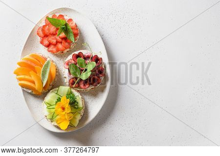 Puffed Rice Cakes With Different Toppings Friuts And Vegetables On White Background, Flat Lay. Space