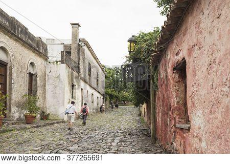 Colonia Del Sacramento / Uruguay; Jan 2, 2019: Tourists Walking Down A Cobblestone Street In The His