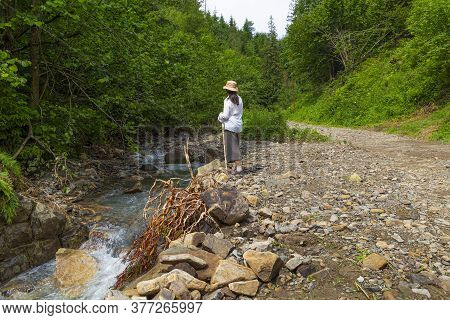 Woman - Hiker In The Forest  Near The Small Mountain River. Summer Holidays In The Carpathian Mounta