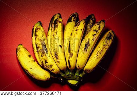 Bunch Of Overly Riped Bananas On Red Background. Fresh Organic Banana, Fresh Bananas On Kitchen Tabl
