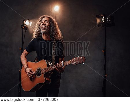 Talented Hispanic Musician In Black T-shirt Playing Guitar. View Of Musician In The Spotlight