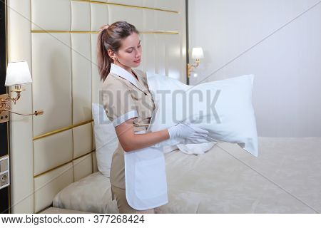 The Maid Is Holding A Pillow. Change Of Bed Linen In The Hotel Room. The Concept Of Cleaning. Copy O
