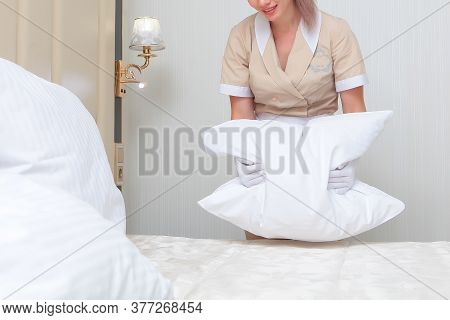 The Maid Is Holding A Pillow. Change Of Bed Linen In The Hotel Room. Unrecognizable Photo. The Conce
