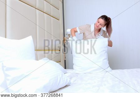 A Young Maid In Uniform Straightens A Pillow In The Bedroom.the Concept Of Cleaning And Hospitality