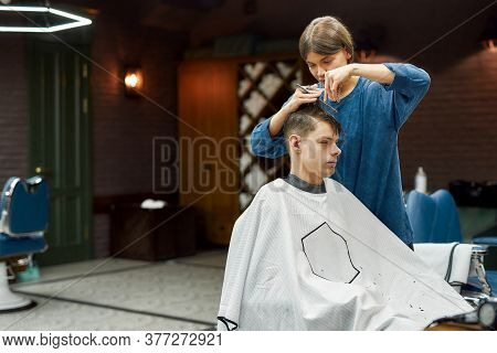 Serving Client In Barbershop. Professional Female Hair Stylist Making Trendy Haircut For A Young Cau