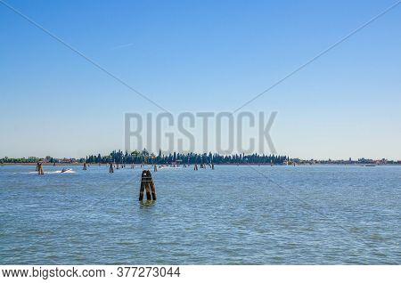 Panoramic View Of San Francesco Del Deserto Island In Venetian Lagoon Water With Wooden Poles. View