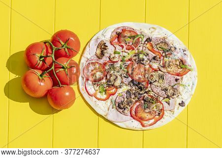 Daylight. The Bright Sun Puts A Red Tomato On The Branches. On A Yellow Background Lies A Blank For