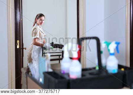 Room Service.a Uniformed Maid Cleans The Room.maids Cart With Work Supplies. Copy Of The Number.copy