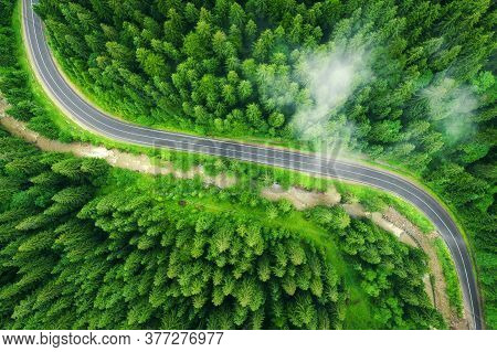 Aerial View Of Road In Beautiful Green Forest In Low Clouds At Sunset In Summer. Colorful Landscape