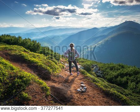 Beautiful Mountains And Standing Young Woman With Backpack On The Trail At Sunset In Summer. Landsca