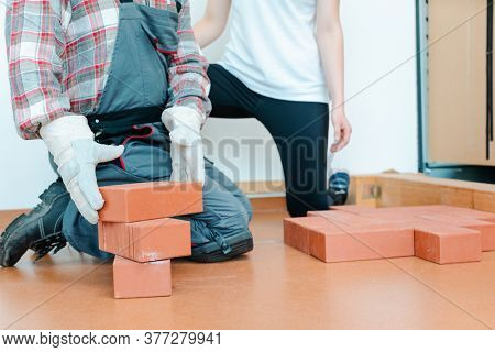 Worker in occupational therapy re-learning to lay bricks in real life training