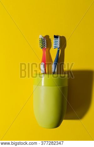 Two Toothbrushes In A Green Glass On A Yellow Background. Red And Blue Toothbrushes. Protection Agai