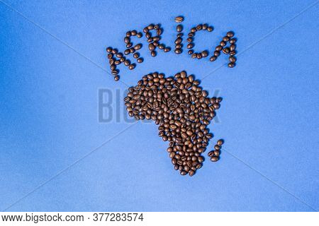 Roasted Coffee Beans. The Contour Of The Mainland Of Africa Is Made Of Coffee Beans On A Blue Backgr
