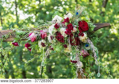 Decor Of A Wedding Arch. Rustic Wedding Arch. Red Flowers On A Green Background