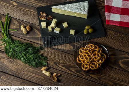 Camembert Cheese. Cheese Dish With Olives, Herbs, Snacks On An Old Black Wooden Table. Brie Cheese.