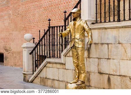 Malaga, Spain - September 03, 2015: Street Performer Suits Up Entirely Gold In The Streets Of Malaga