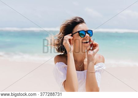 Glad Pretty Woman In Sparkle Sunglasses Expressing Happiness At Resort. Outdoor Shot Of Good-humoure