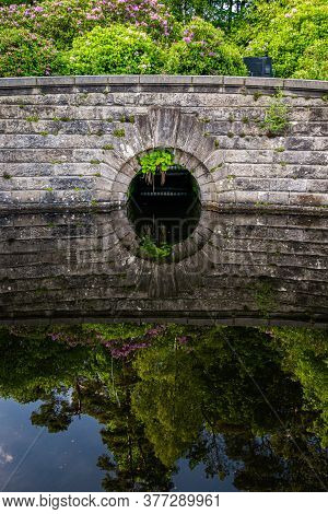 Detail Of An Old Stone Dam Reflecting In Water At Milngavie Waterworks, The Water Treatment Facility
