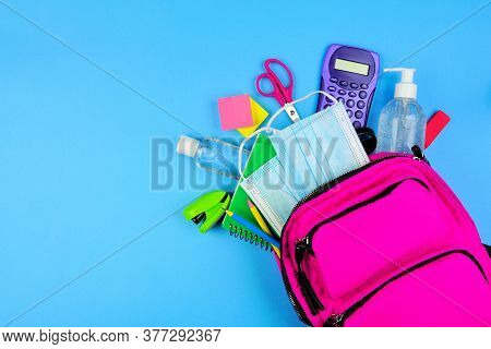 Backpack Full Of School Supplies And Covid 19 Prevention Items. Top View, Spilling Onto A Blue Backg